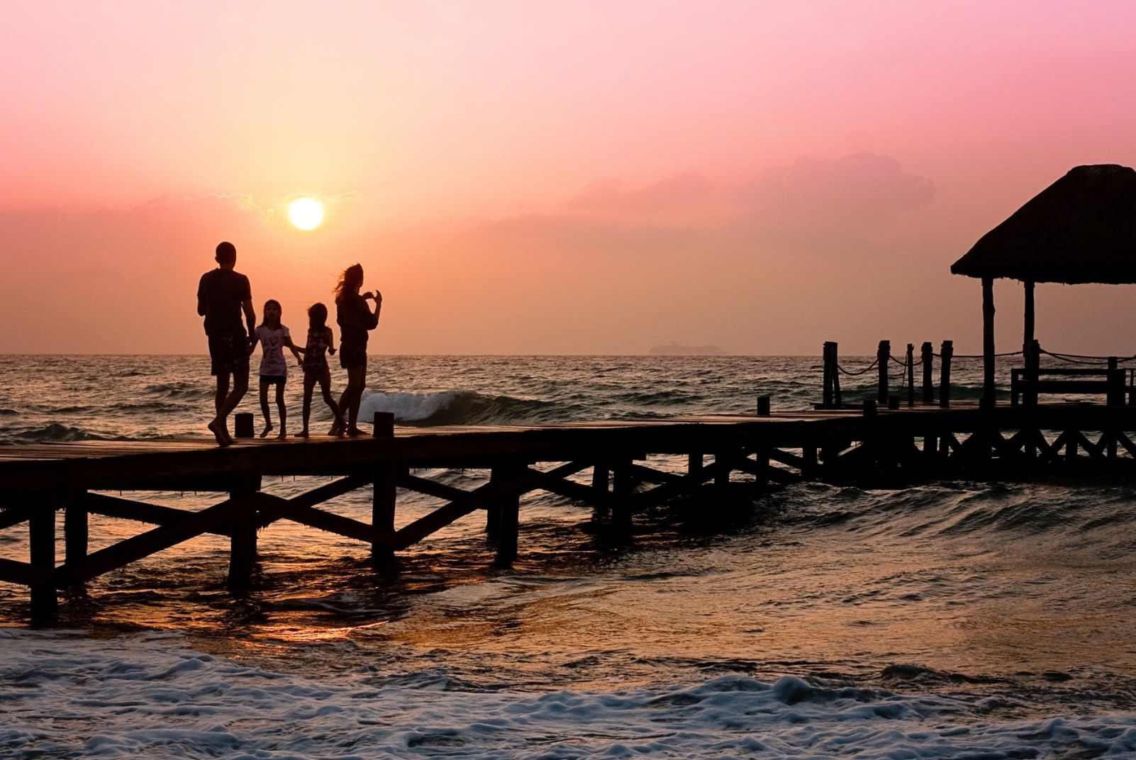 family walking on a pier in front of sunset
